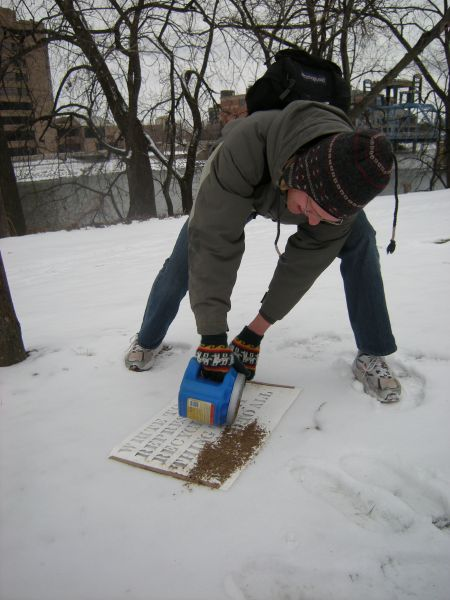 Participant sprinkling dirt over stencil
